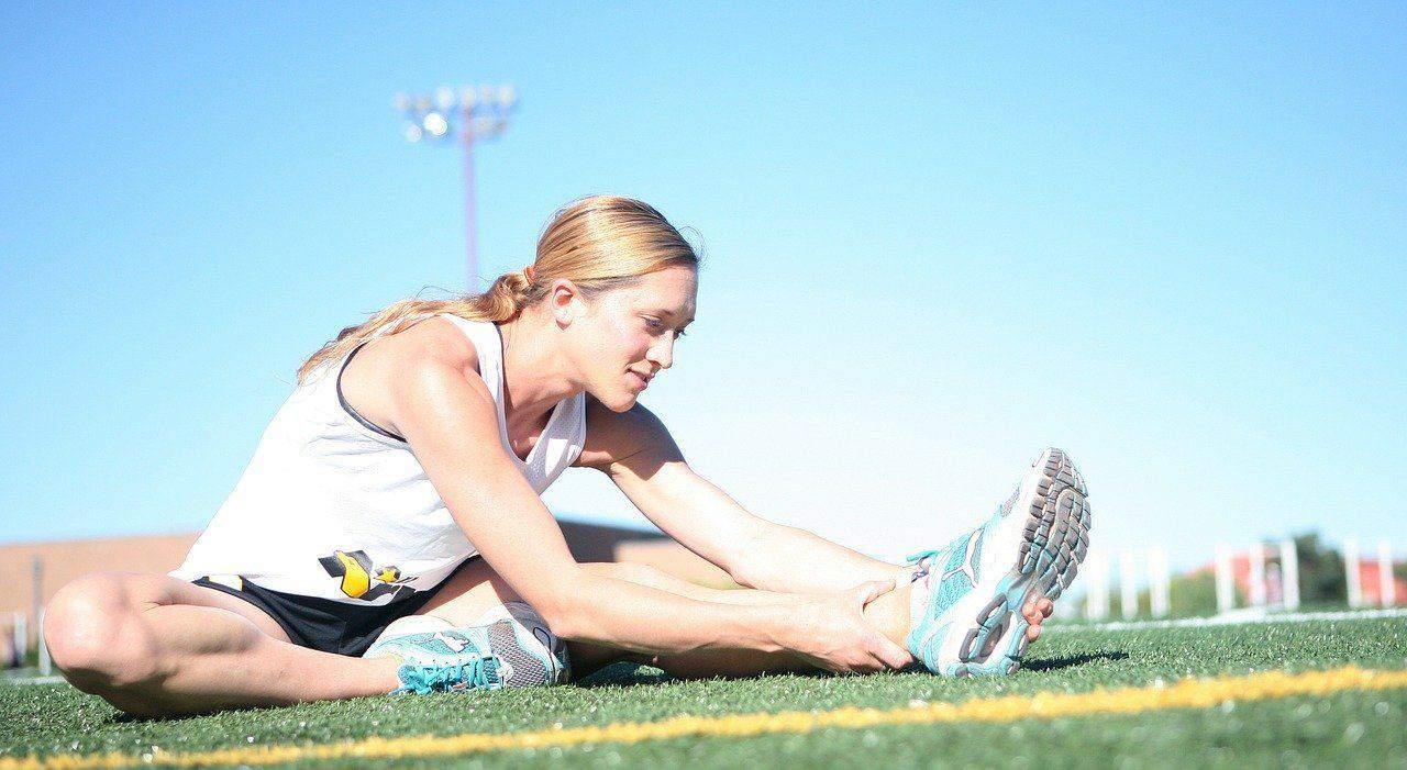 runner stretching her leg muscles
