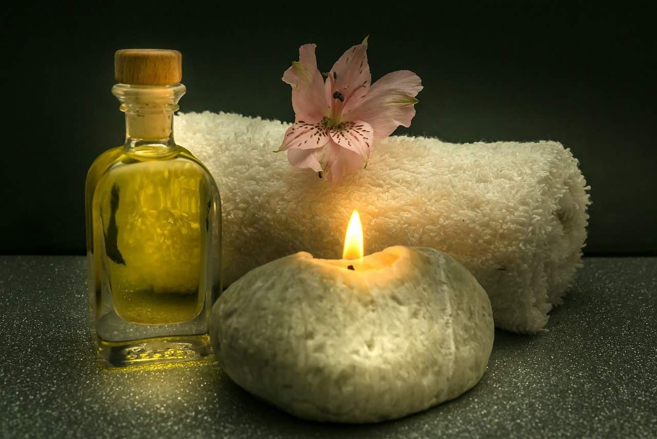 bottle of massage oil, lit candle, and towel - ready for a massage at home
