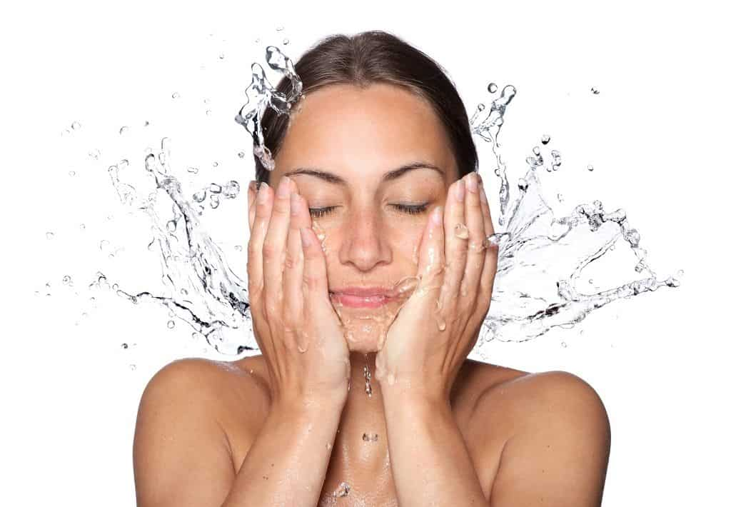 woman washing her face to prepare for the aloe vera face mask