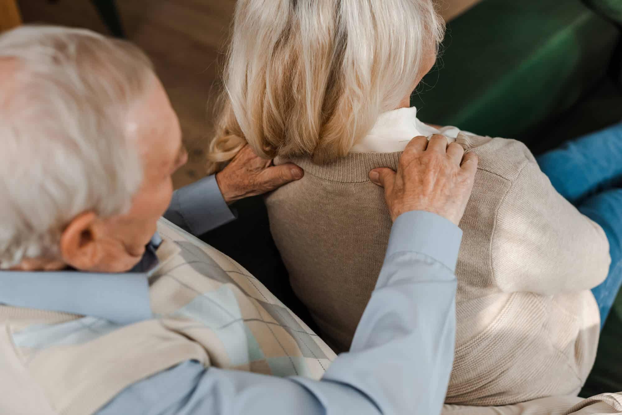 older man giving an older woman a shoulder massage at home