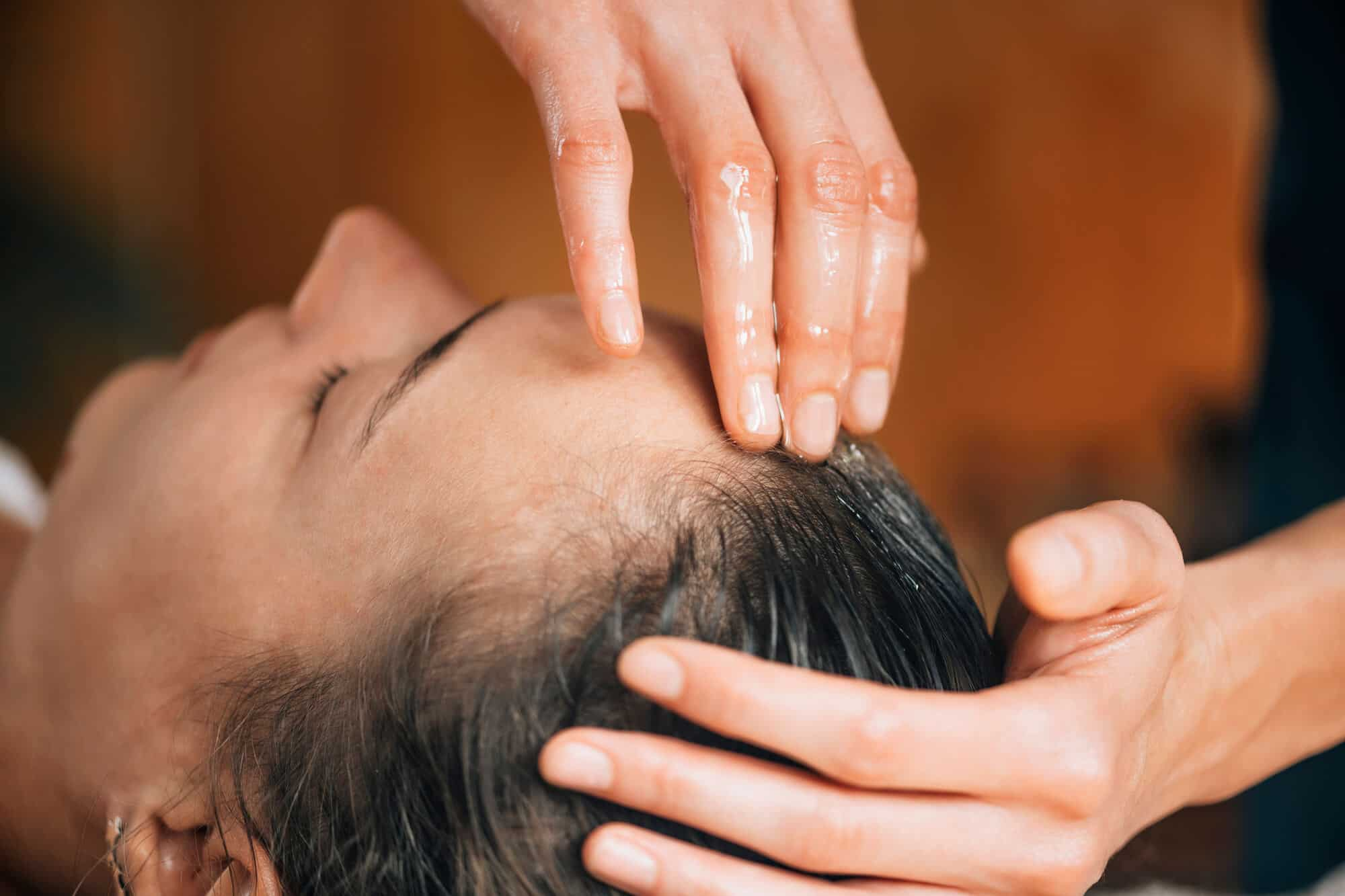 woman getting scalp massage with oil
