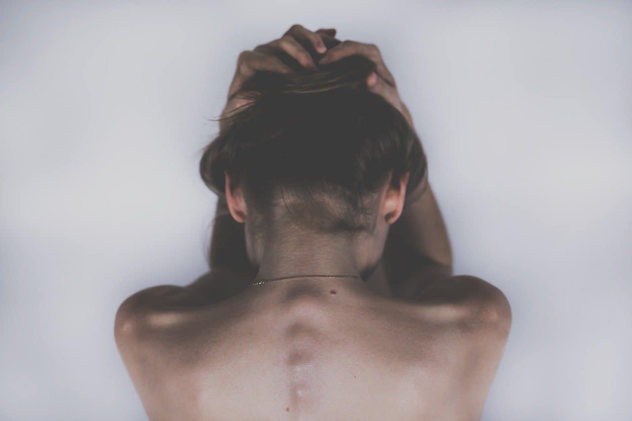 woman holding her head to manage headache pain